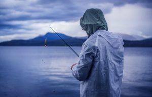 Orang memancing di danau saat hujan