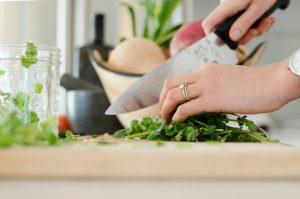 Mengiris sayur dengan pisau untuk memasak