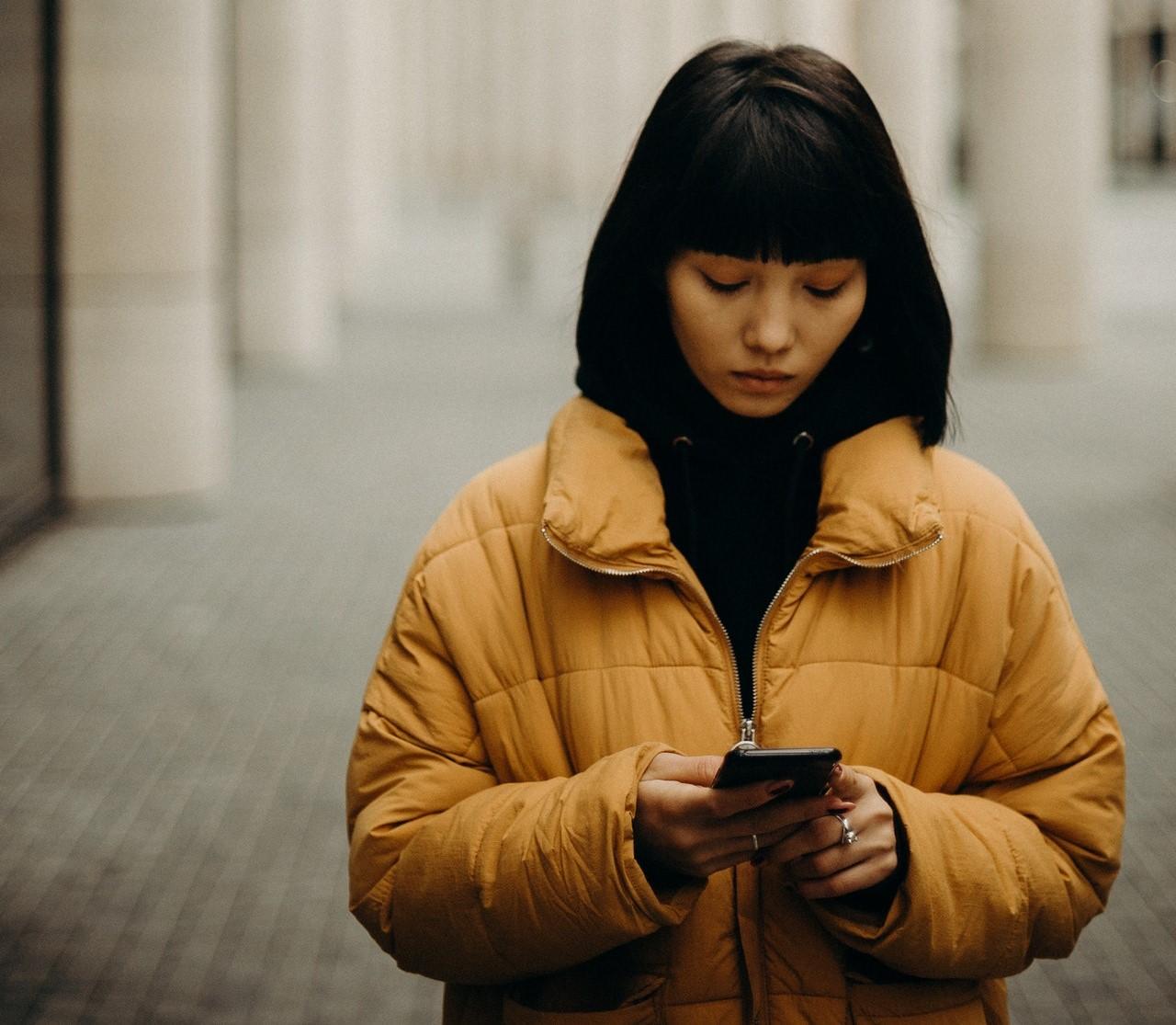 Wanita putus cinta menatap ponsel